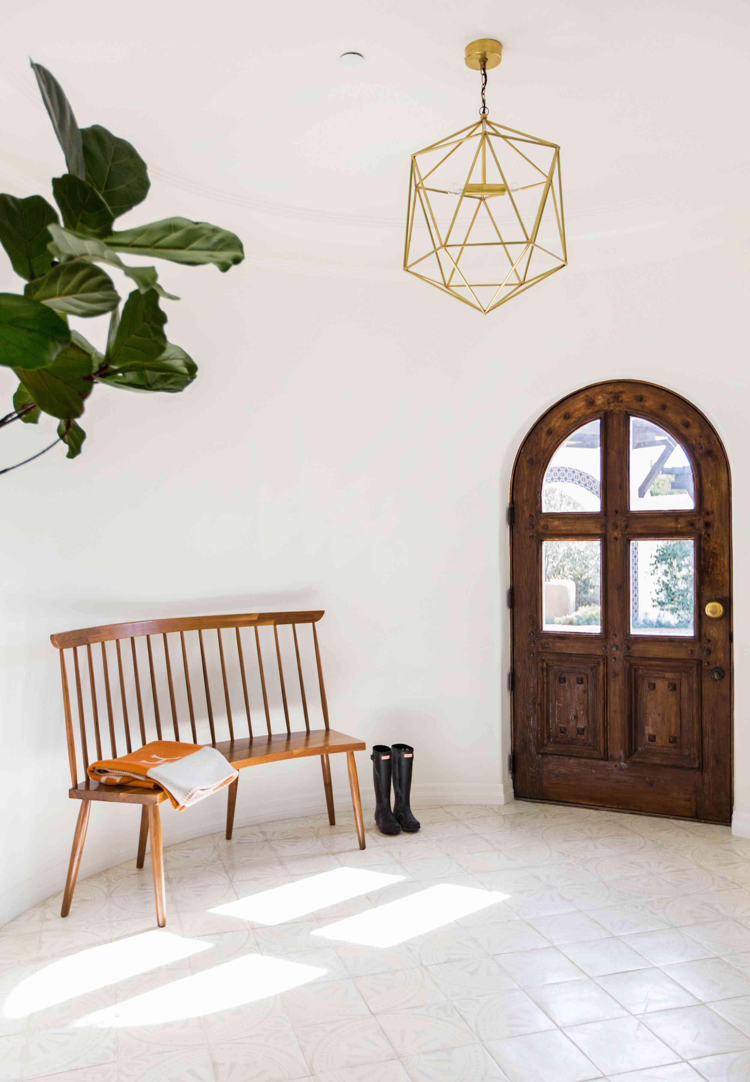 entryway with wooden rounded door, golden chandelier, wooden bench