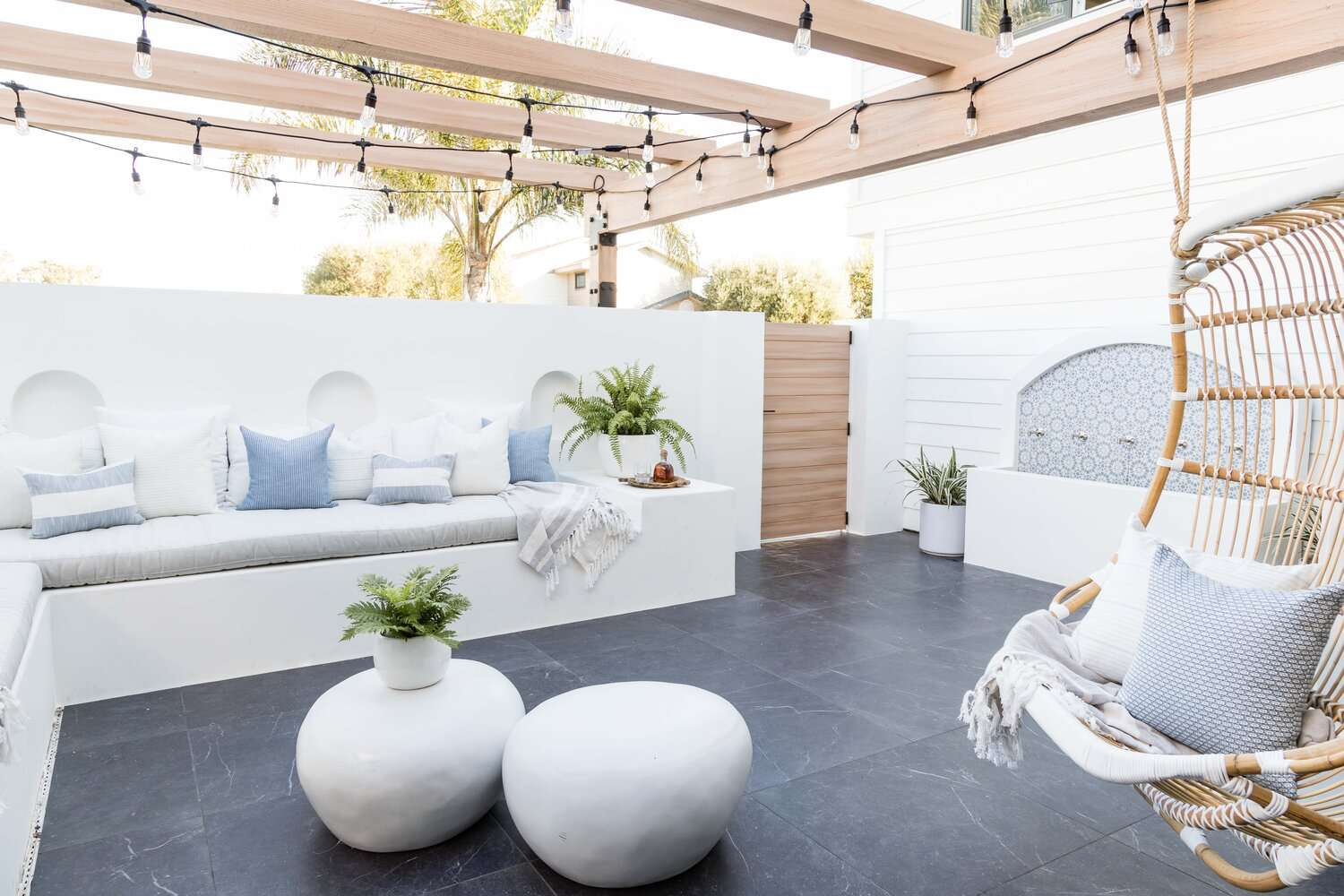 Outdoor patio with stylish hanging chair.