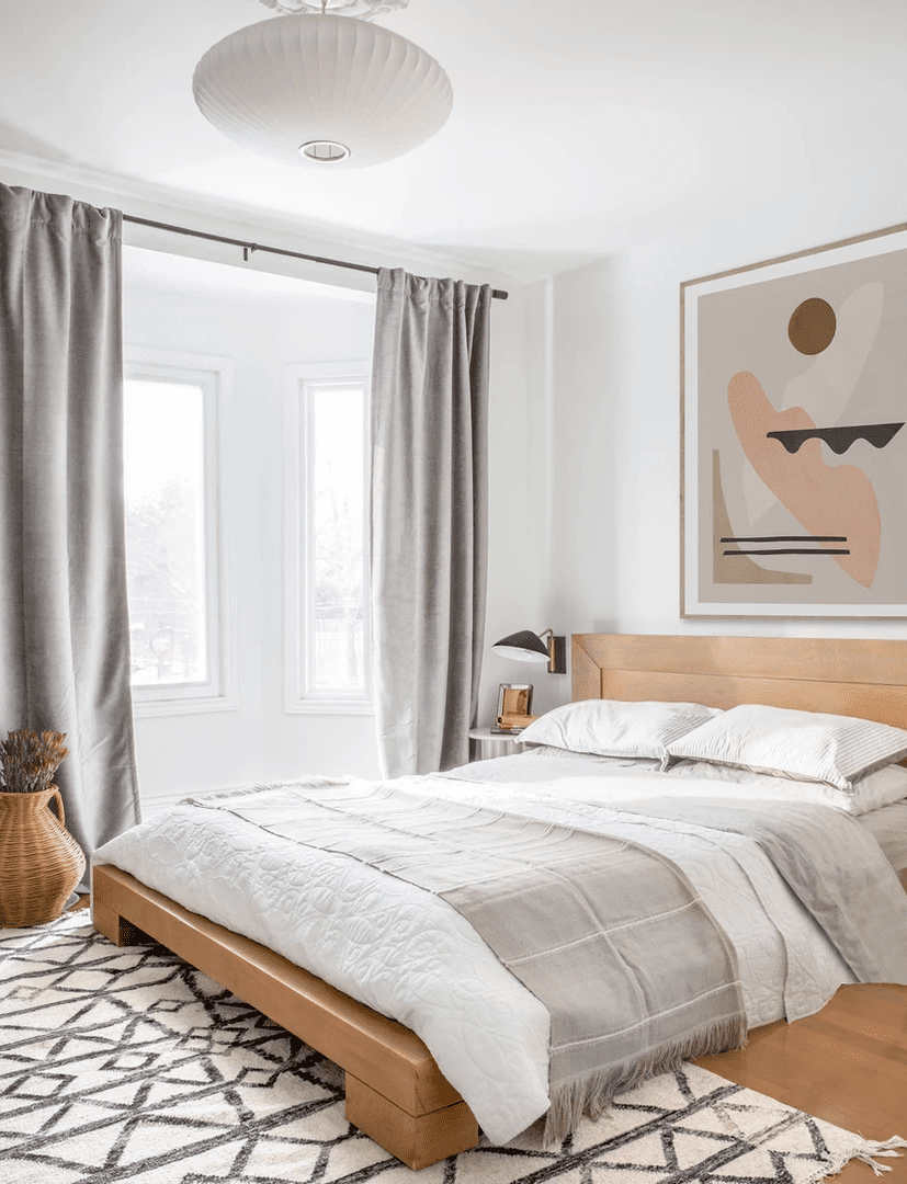 Neutral bedroom with low bedframe and printed art.