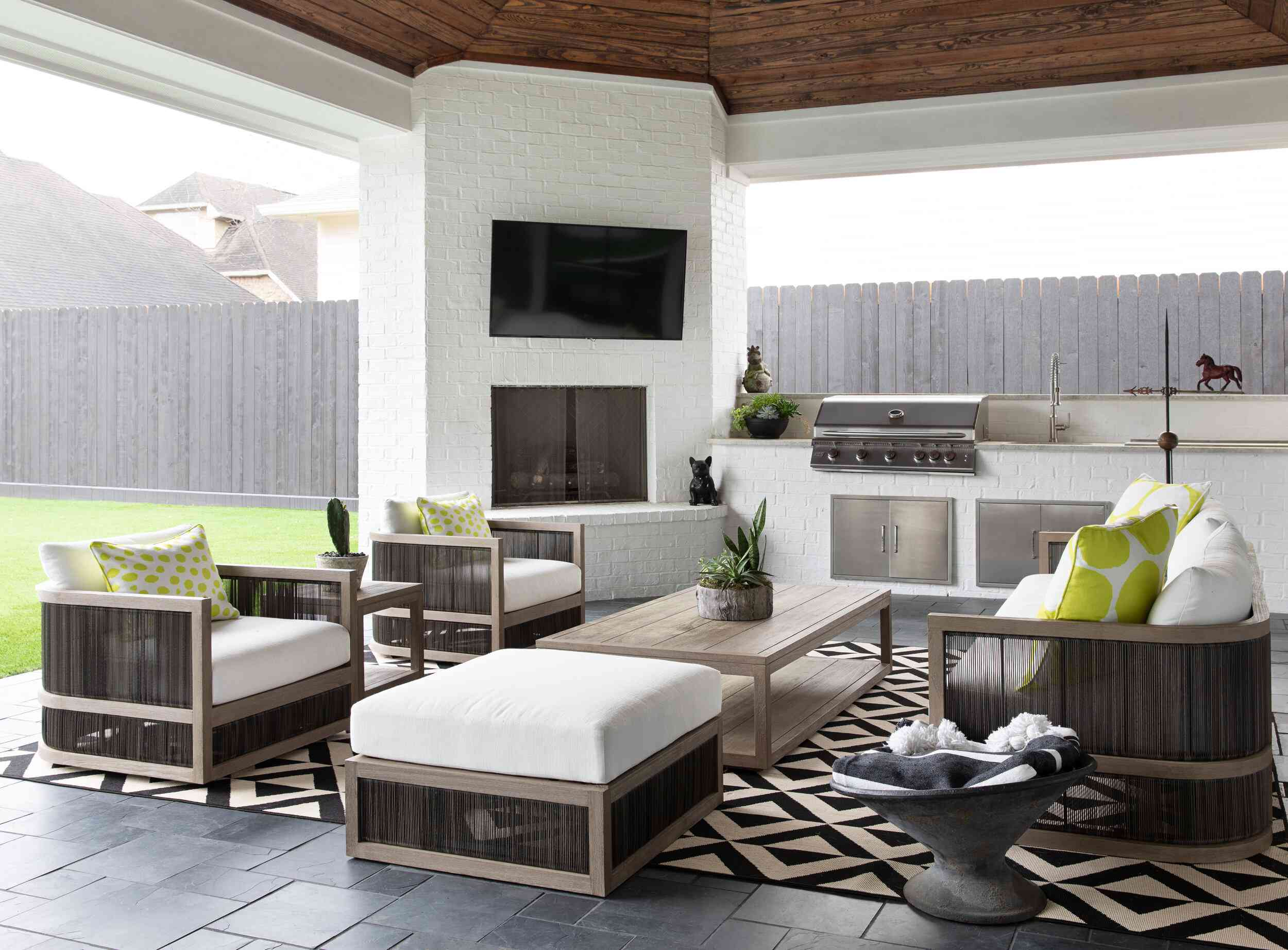 A covered porch with an outdoor fireplace, an outdoor kitchen, and a large TV