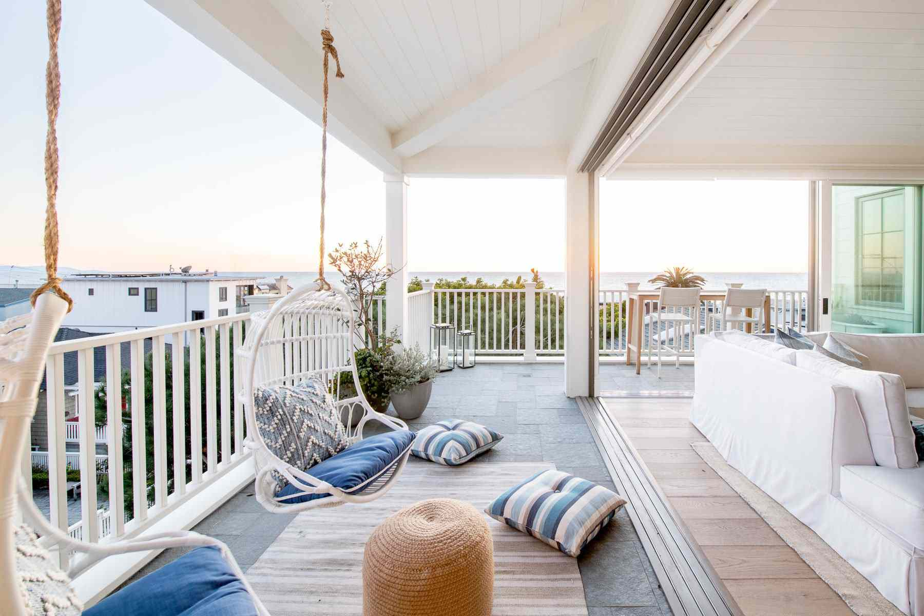 A large outdoor deck with two porch swings and a couch