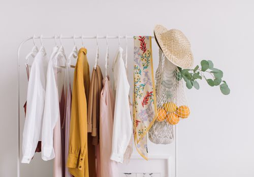 Clothes, scarf, and straw hat hang from a clothes rack