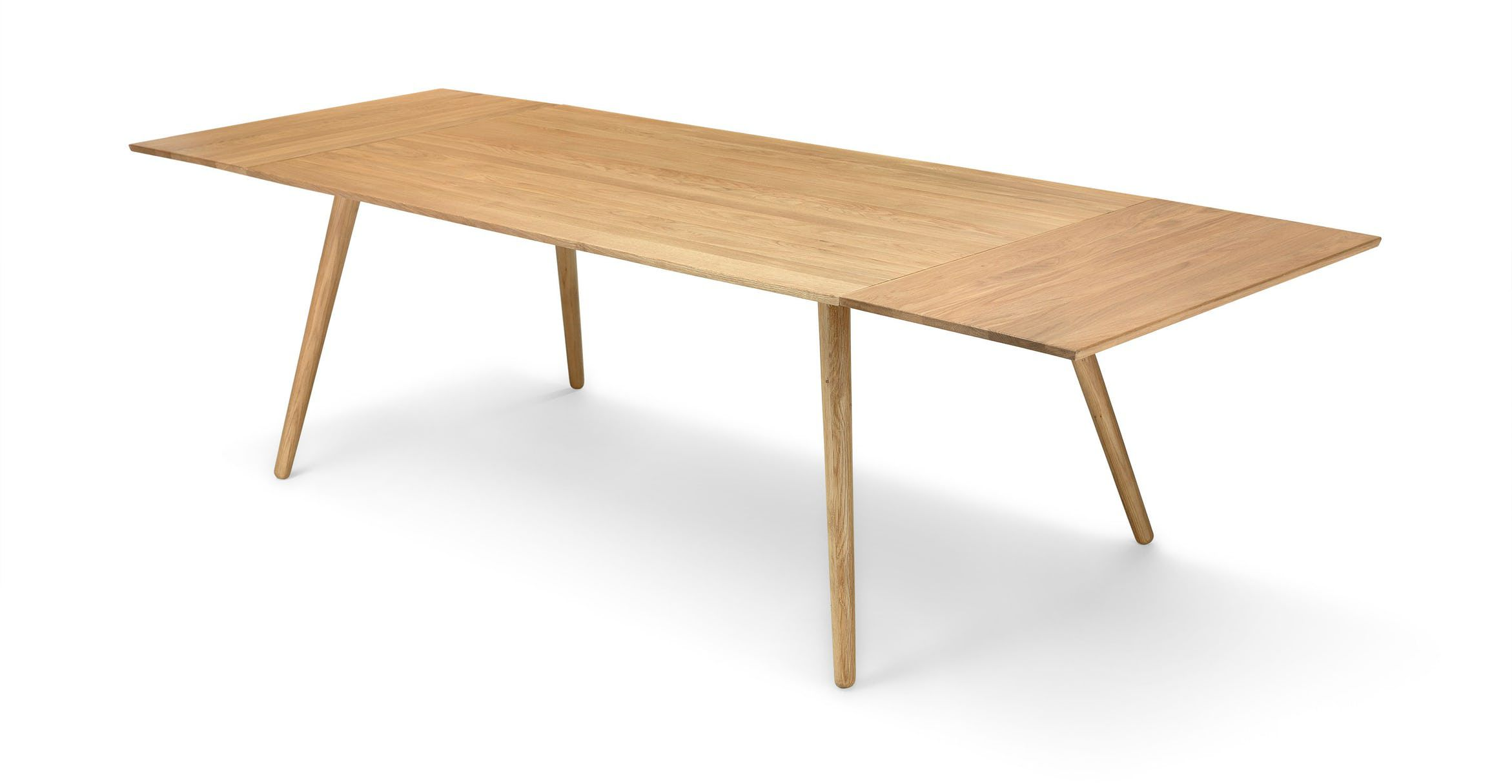 A long, midcentury modern style dining table in light oak finish with tapered legs.