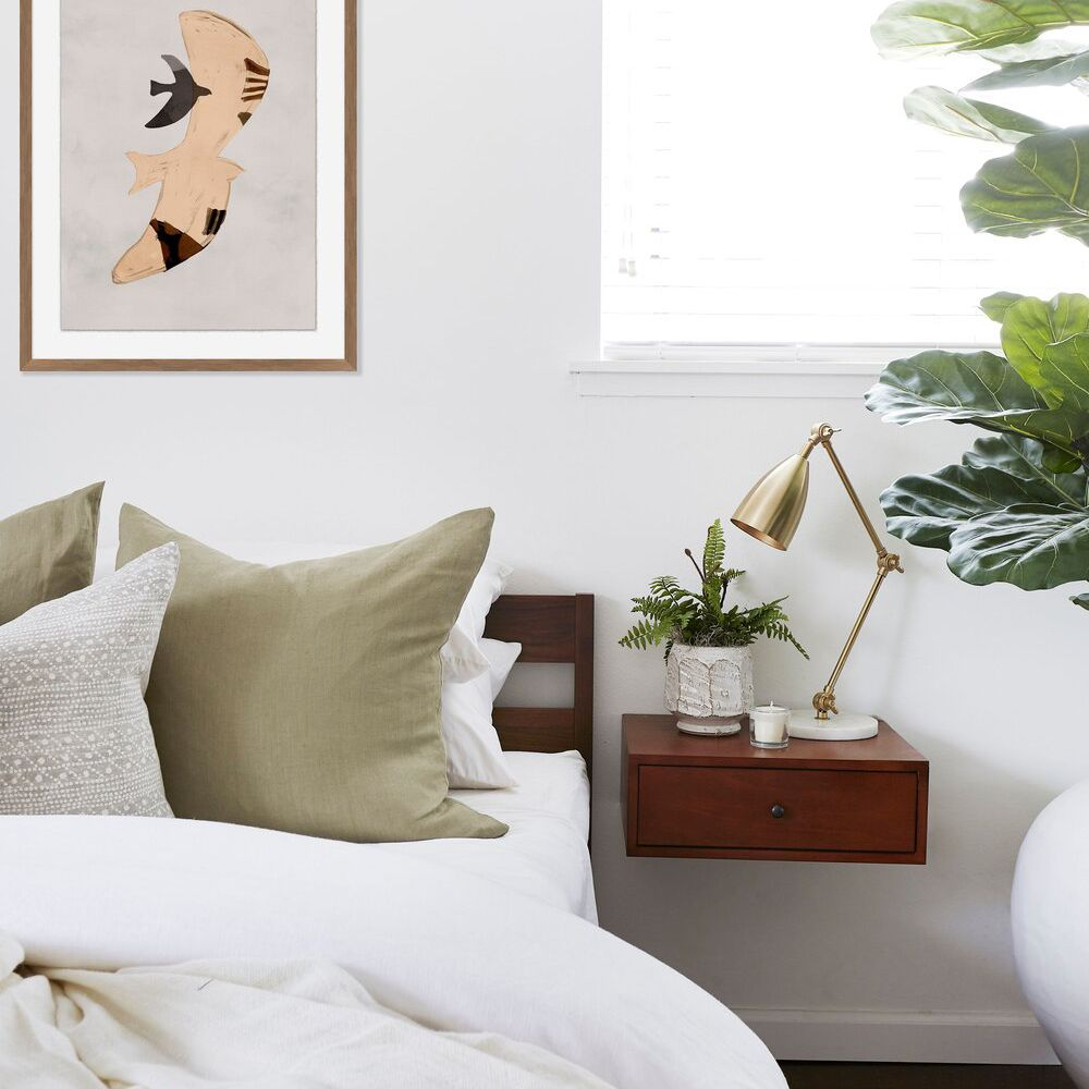 A minimalist bedroom with a sleek gold desk lamp