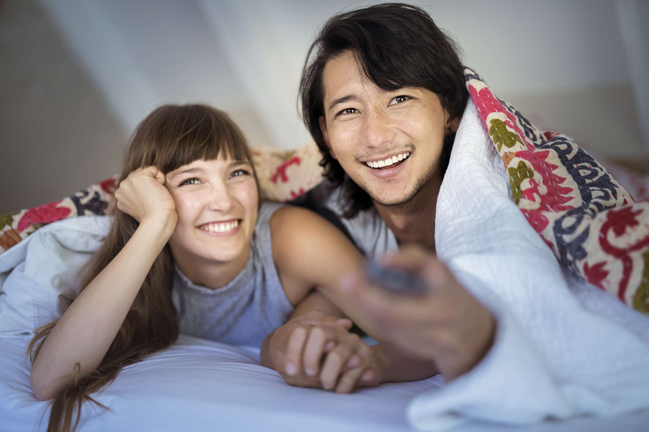 Young couple watches TV in bed