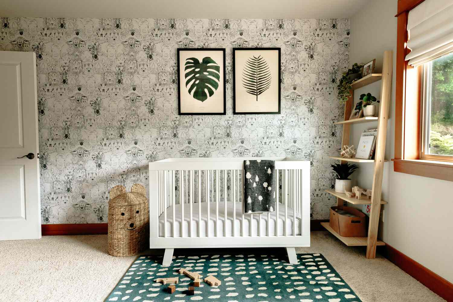 nursery with green pattern wallpaper and leaf art prints