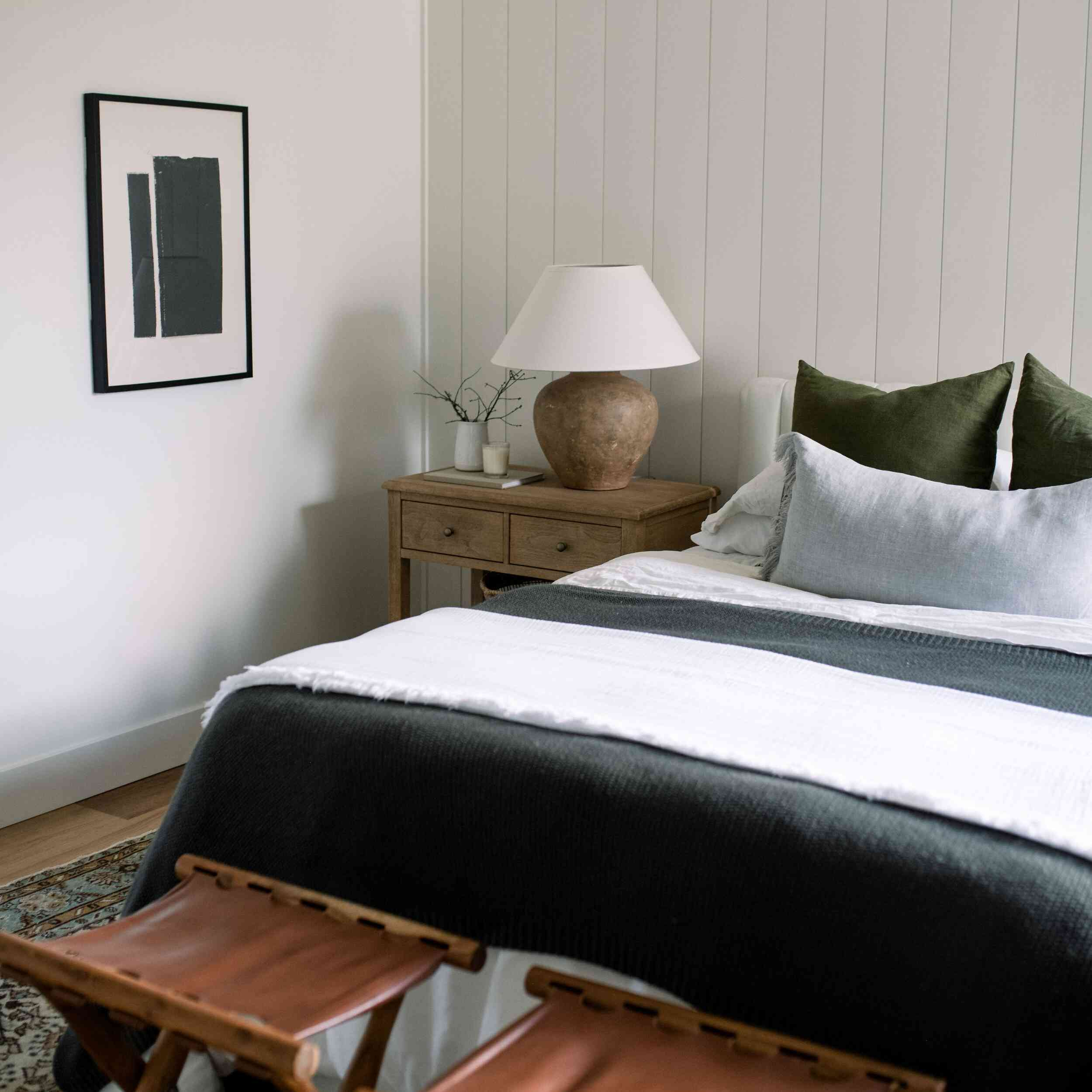 Modern bedroom with light gray paneling and rustic elements