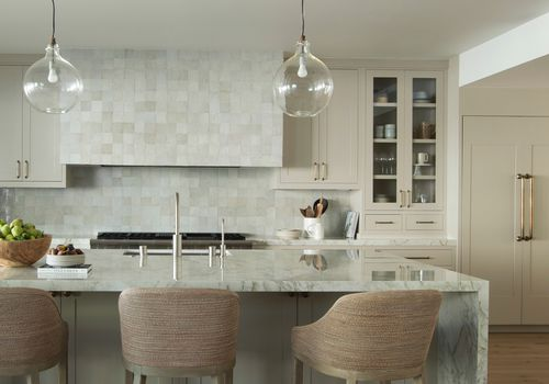 Neutral monochromatic kitchen with marble island.