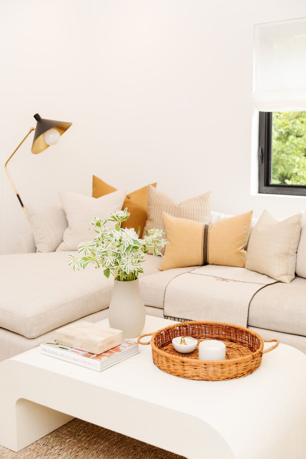 Light beige couch with orange pillows.