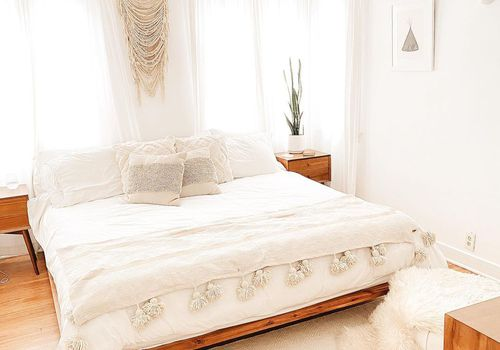 White bedroom with plant on the nightstand