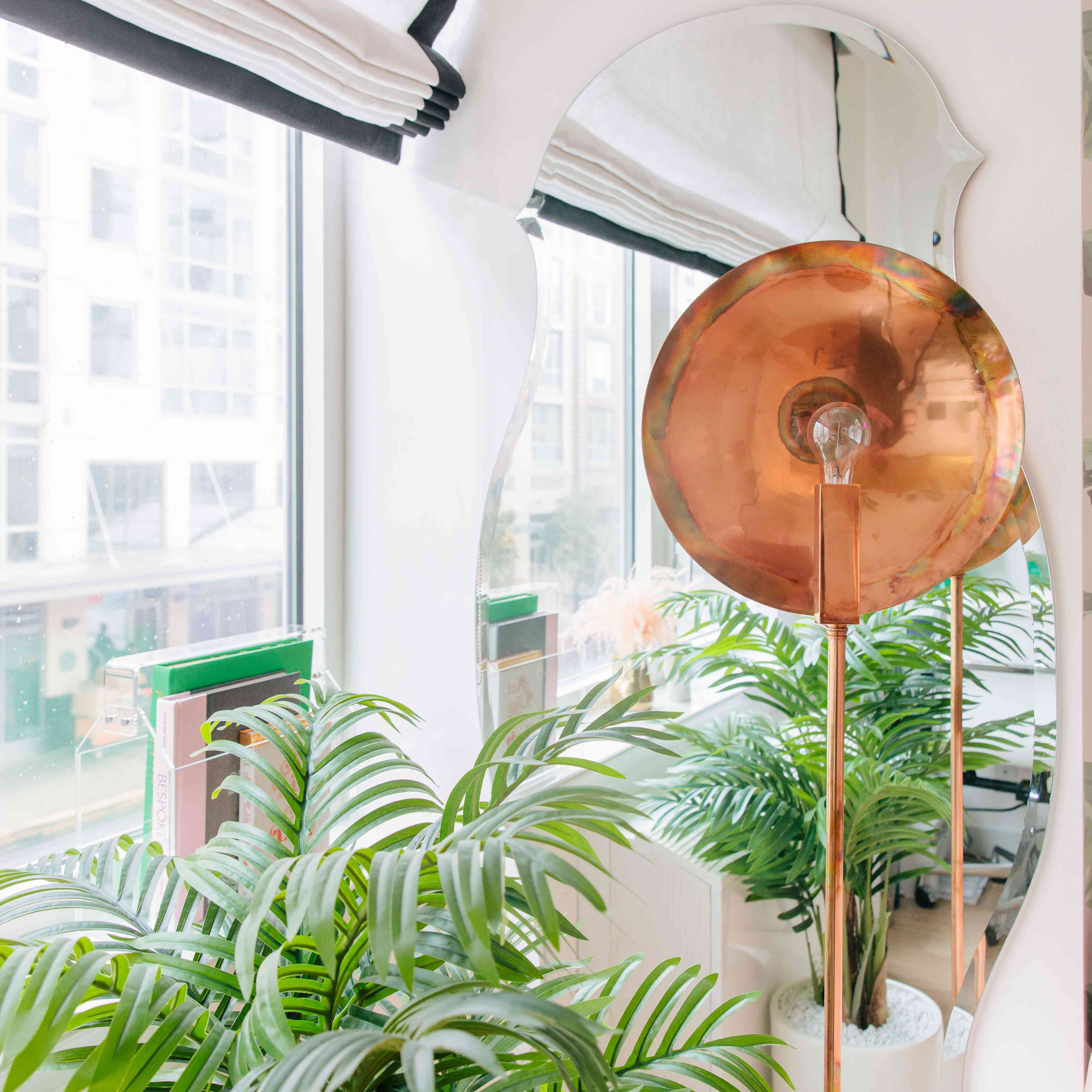 Bronze lamp next to potted palm tree.