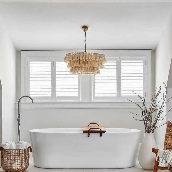 White soaking tub with fringed chandelier, woven basket, accent chair