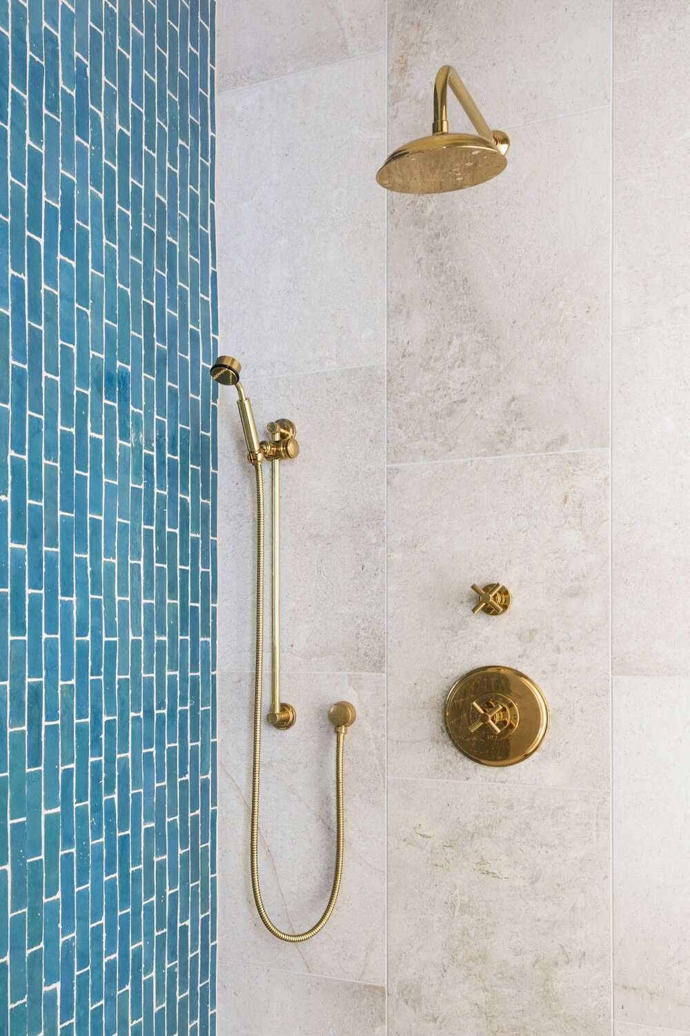 A shower with a beige-tiled wall and a blue-tiled accent wall