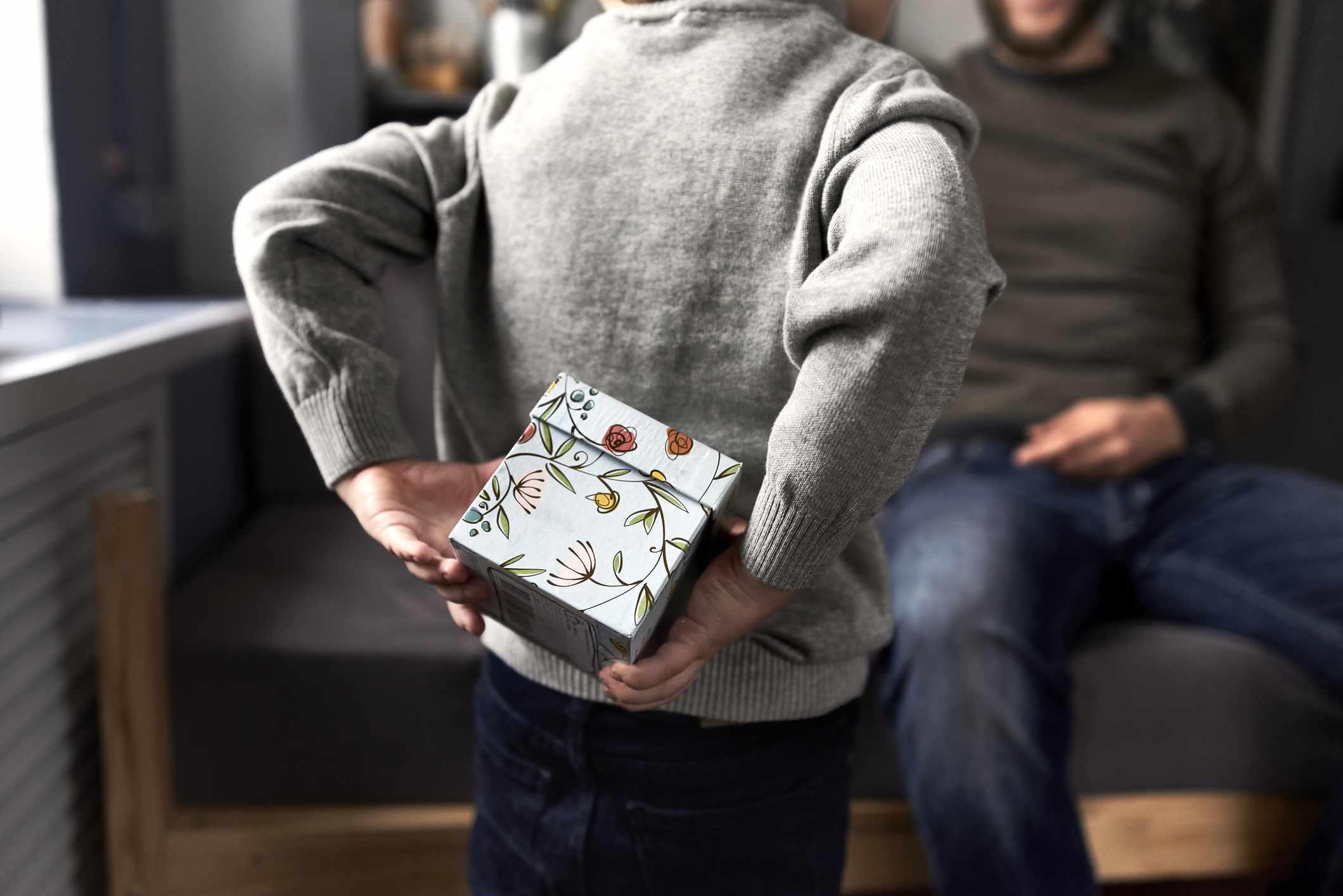 Child hides gift behind back
