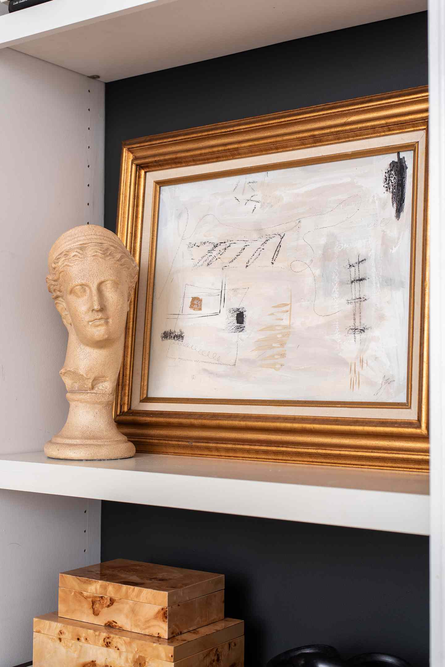 Art in gold frame next to small bust statue.