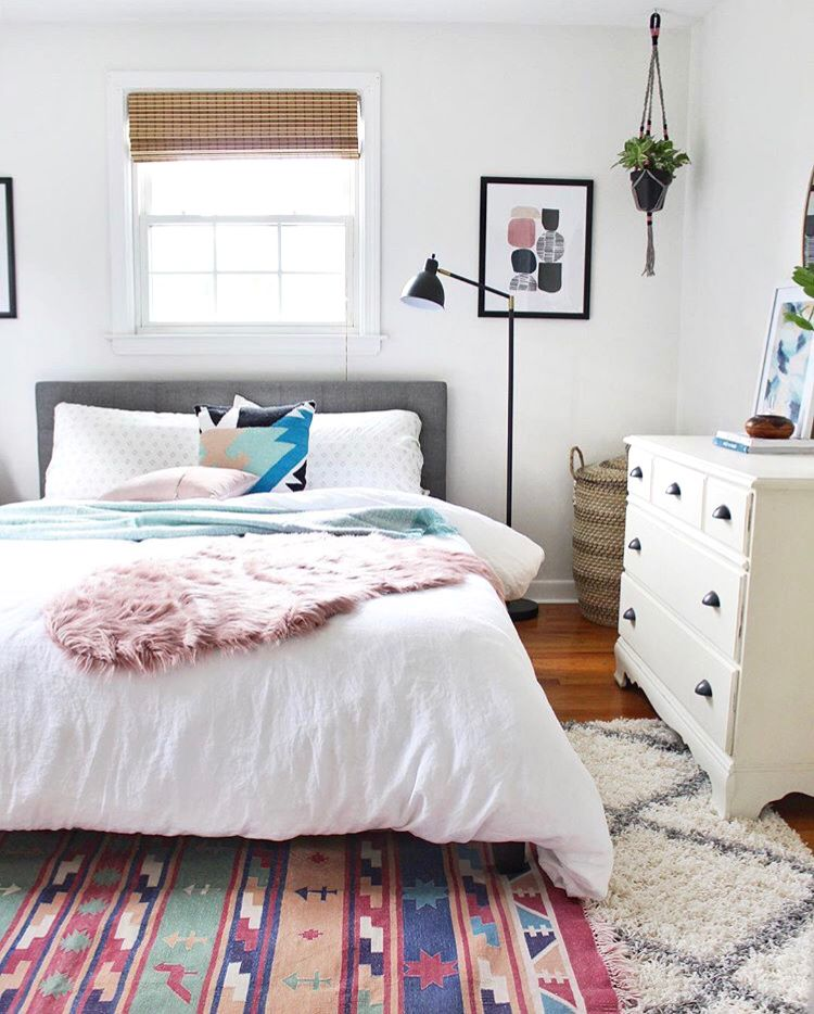 A bedroom with a lavender throw pillow, throw blanket, and work of art