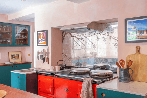 A pink kitchen with teal cabinets and a bright red stove