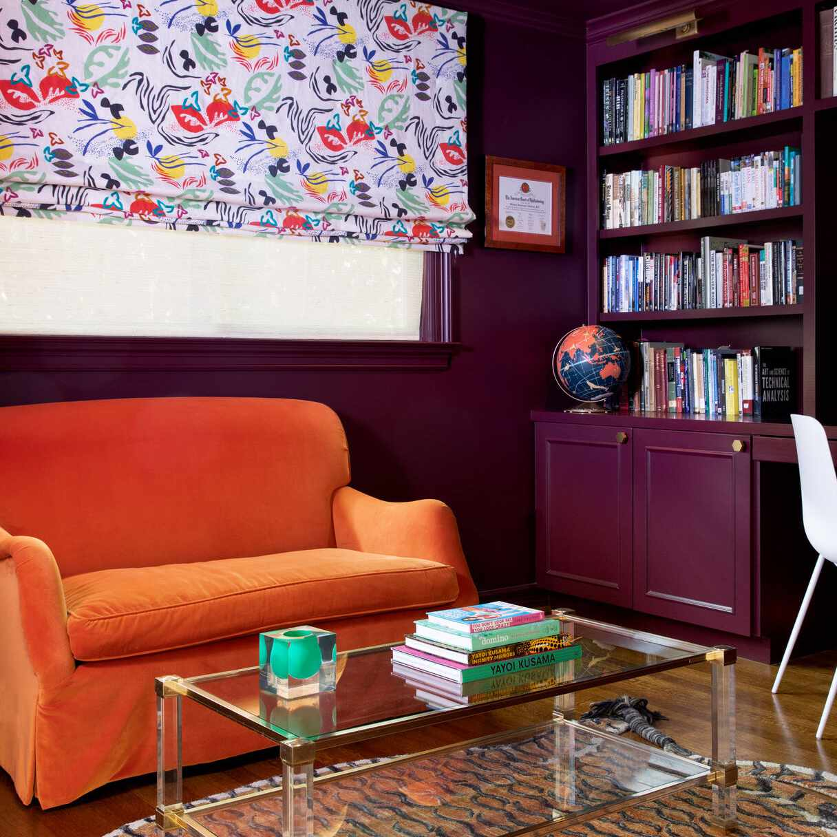purple bookcase with orange couch and decorative curtain