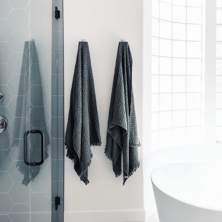 A white bathroom with two slate gray towels hanging on the wall