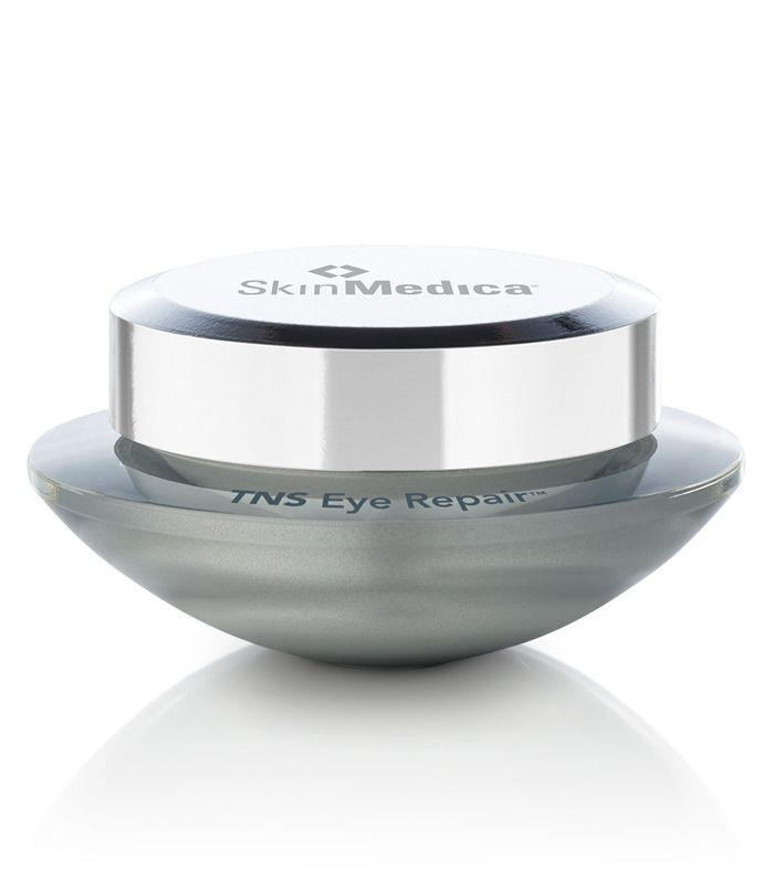 A gray glass container of eye cream with a silver screw top.