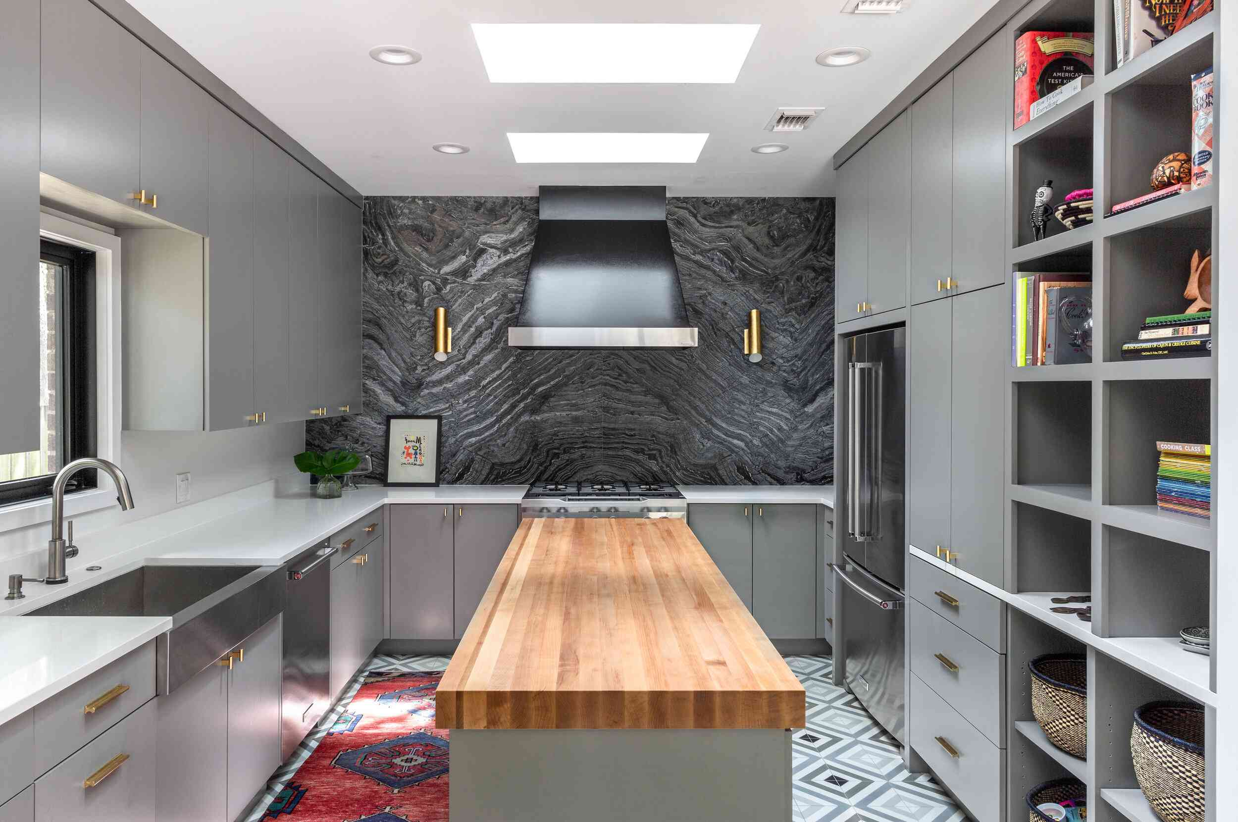 A kitchen with gray cabinets, gray tiled floors, and a charcoal backsplash