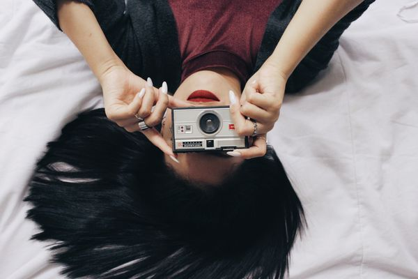 Woman lying and take a picture with a camera