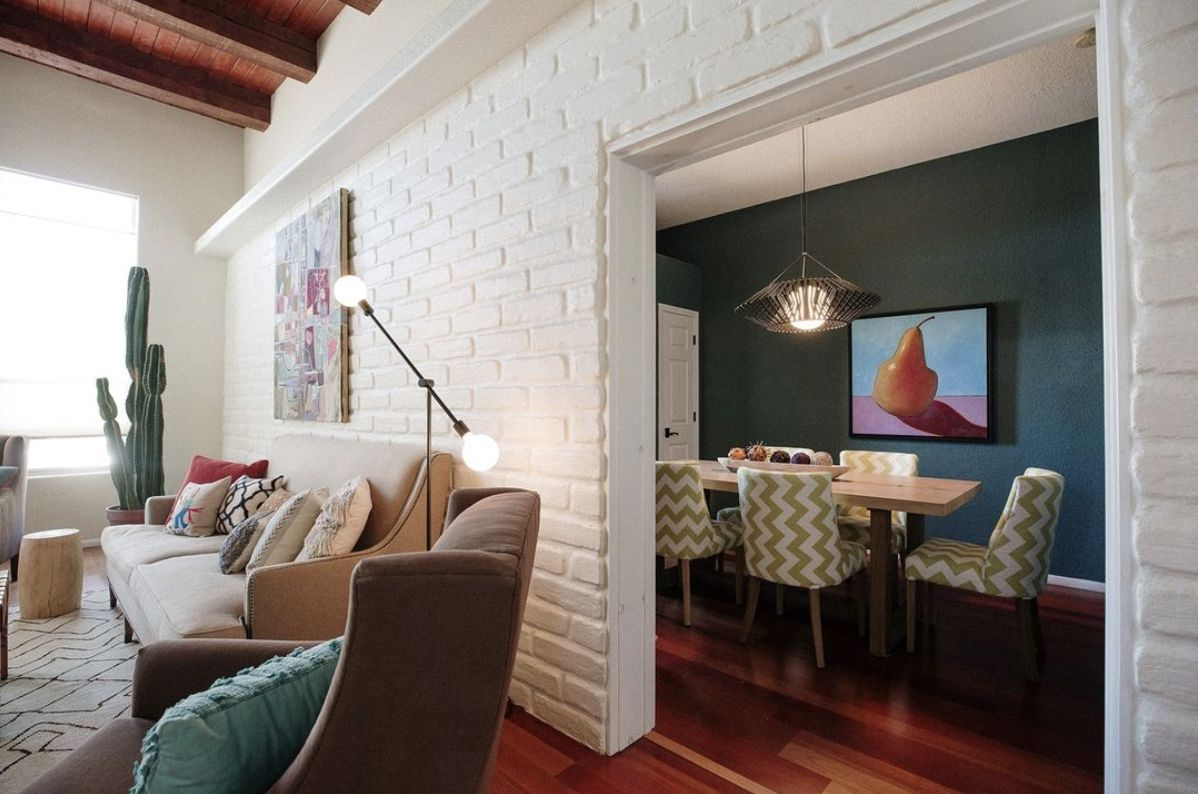 white brick wall dividing living and dining room