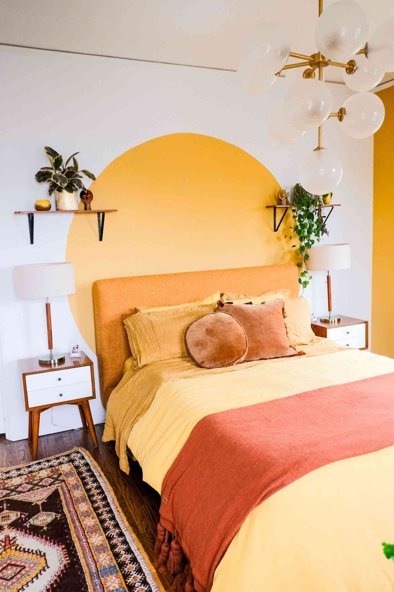 bedroom with yellow circle mural on white wall, yellow bedsheets, floating shelf with plants