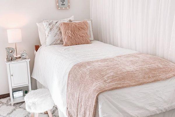 Light pink dorm room bed.