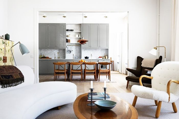White and natural wood color palette are repeated throughout living room and dining area for cohesiveness