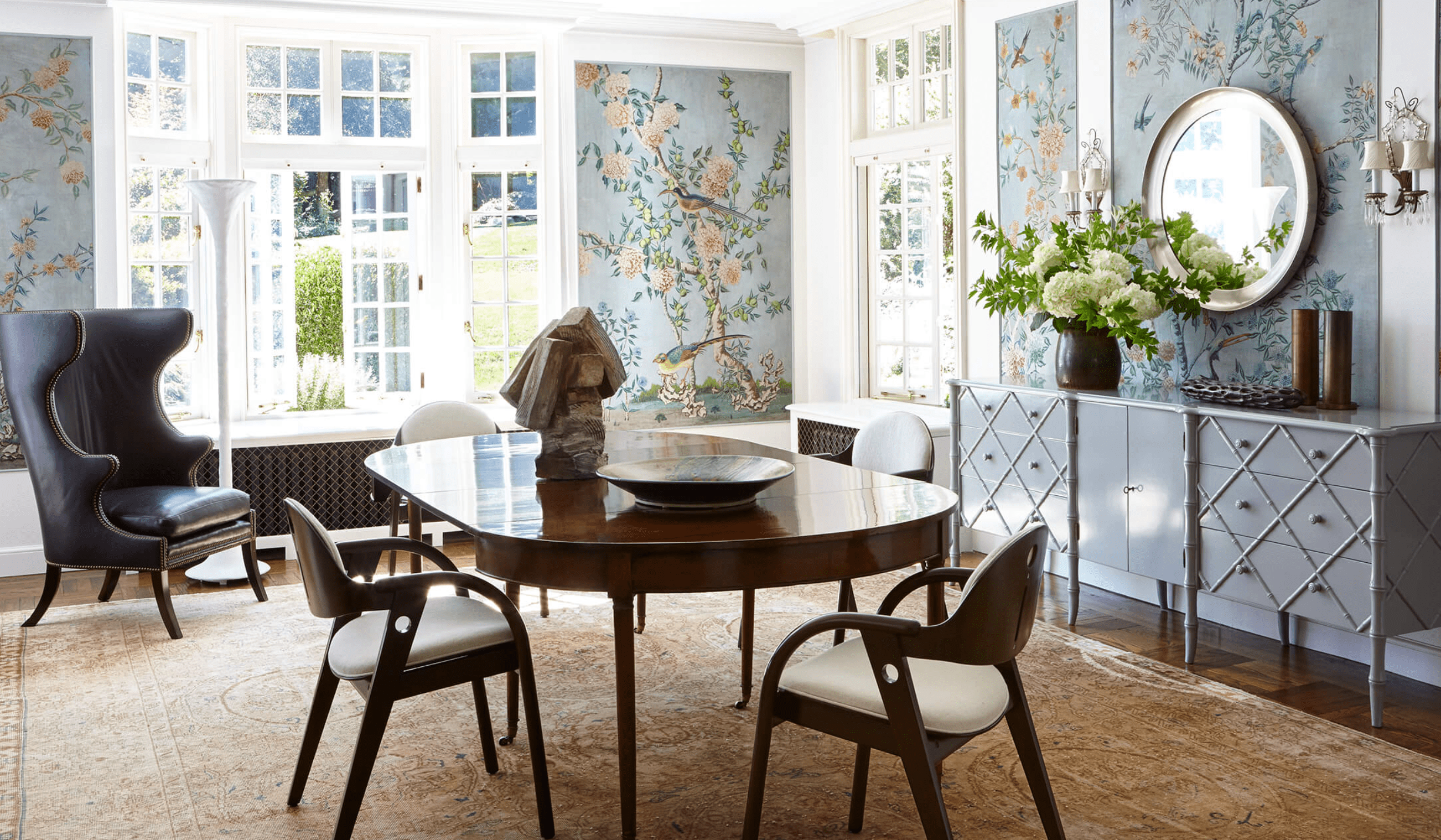 A dining room decorated with light blue floral wallpaper panels