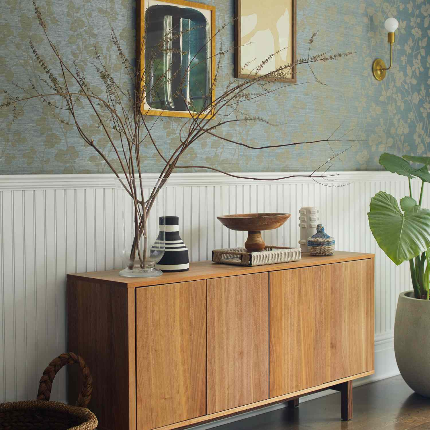 A midcentury modern console table placed in a room lined with light blue wallpaper