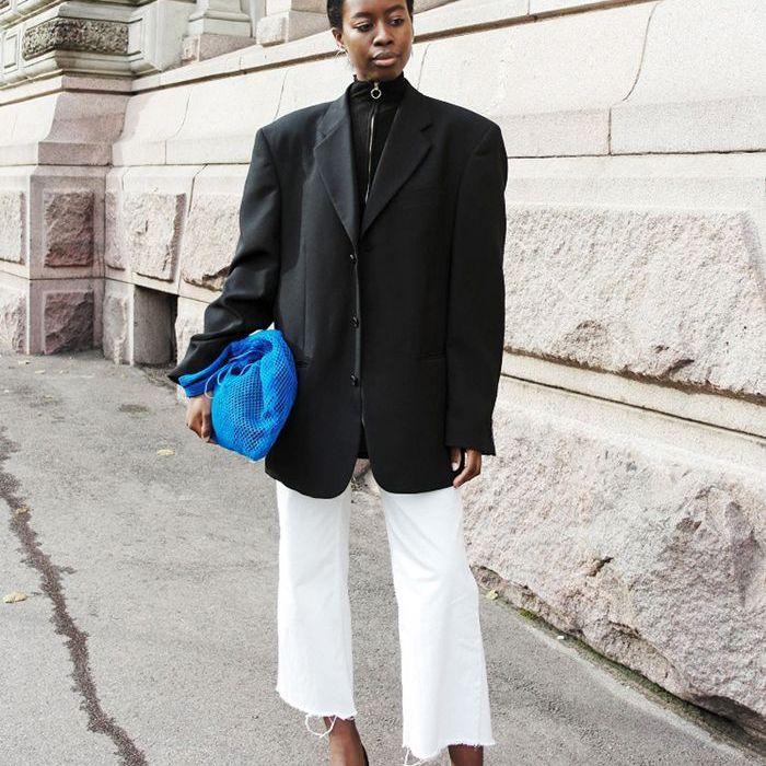 una mujer con chaqueta, jeans cortos y una bolsa azul brillante