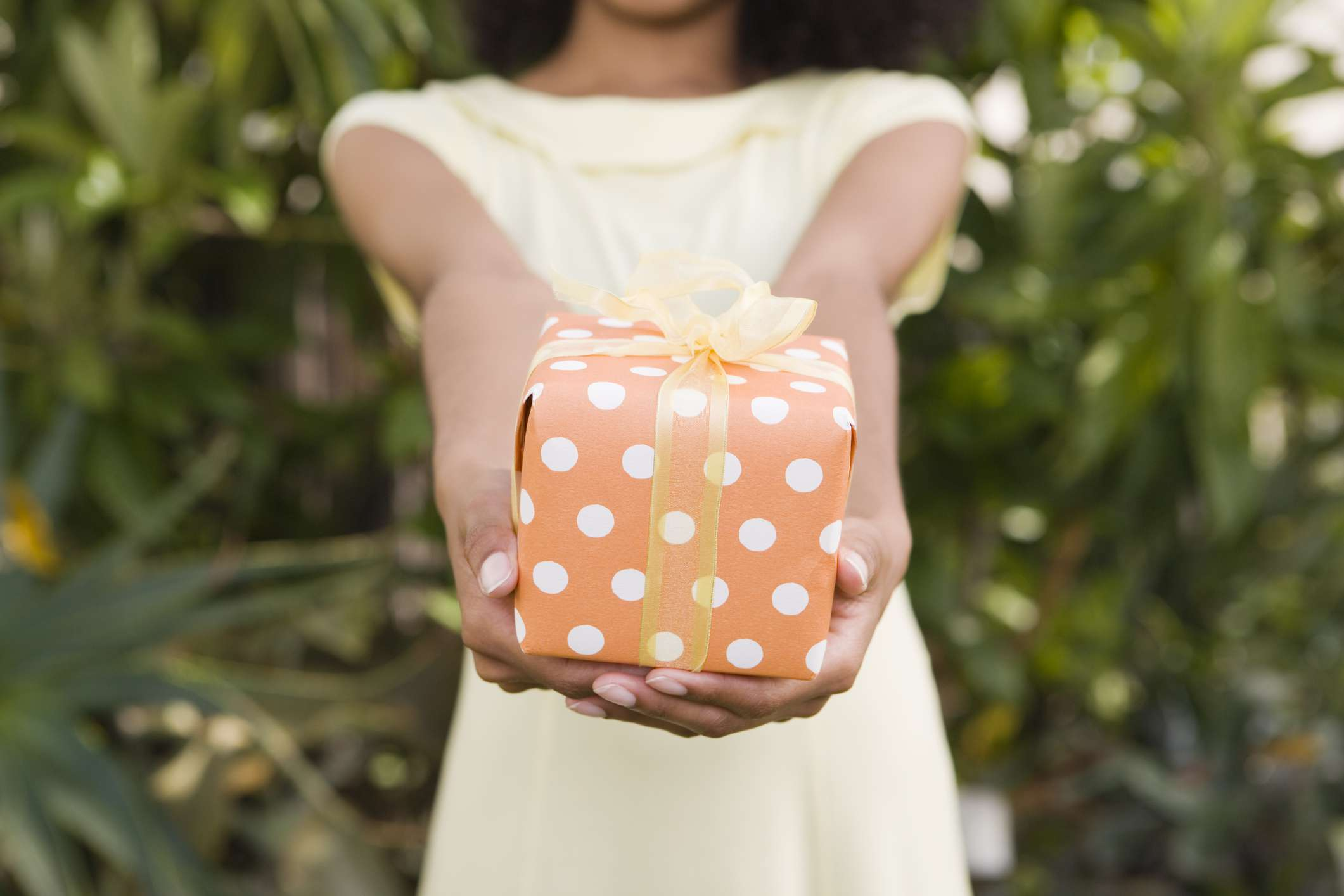 Woman holds out present in polkadot print wrapping