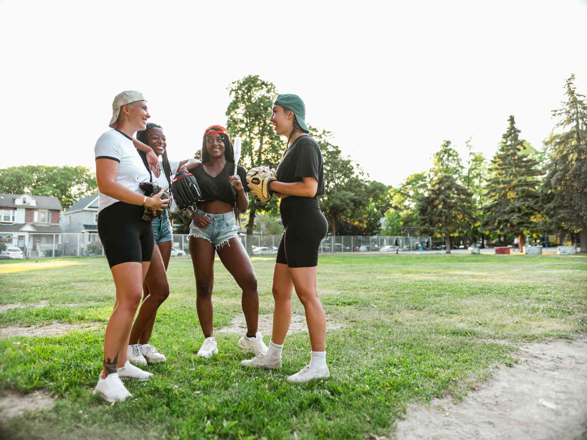Young women gather together, taking break from playing softball