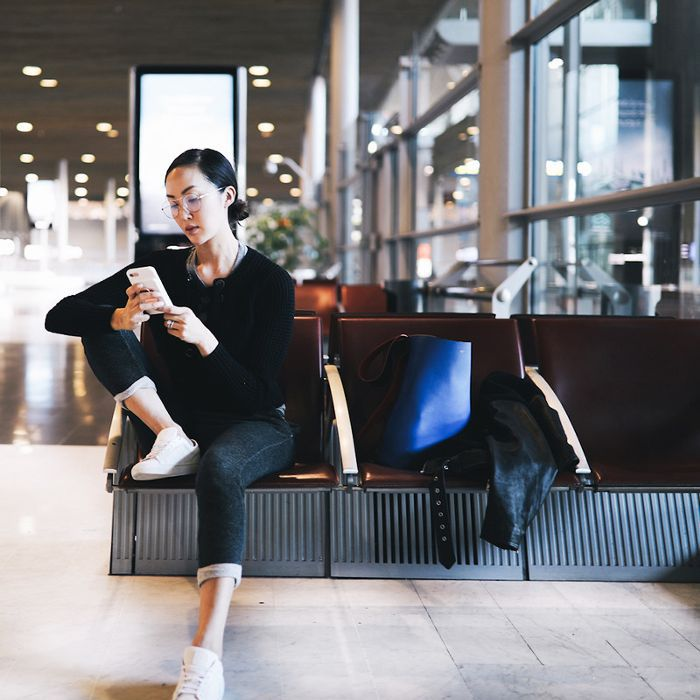 Young woman gazes at her smartphone in airport terminal