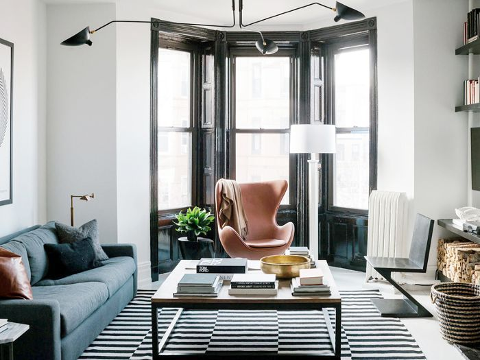 A white walled living room with a blue couch, large black modern chandelier, pink egg chair, and black and white striped rug.