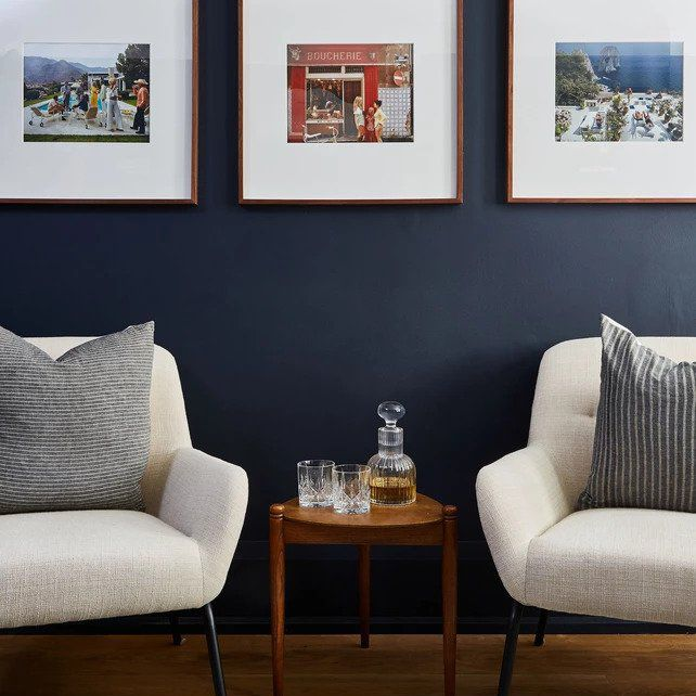 Two chairs set against dark blue wall, framed photographs