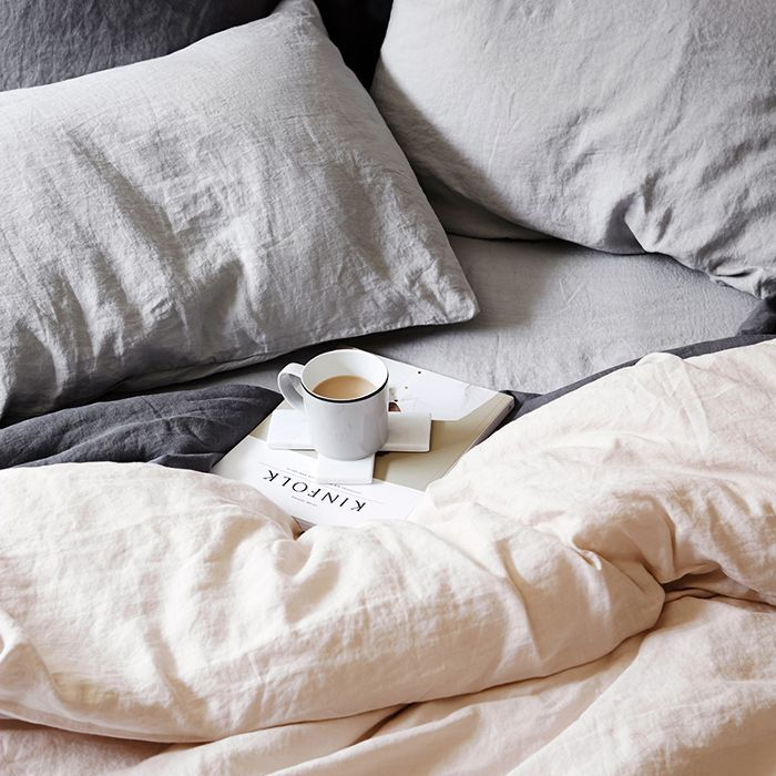 a closeup of an unmade bed and pillows with a cup of coffee