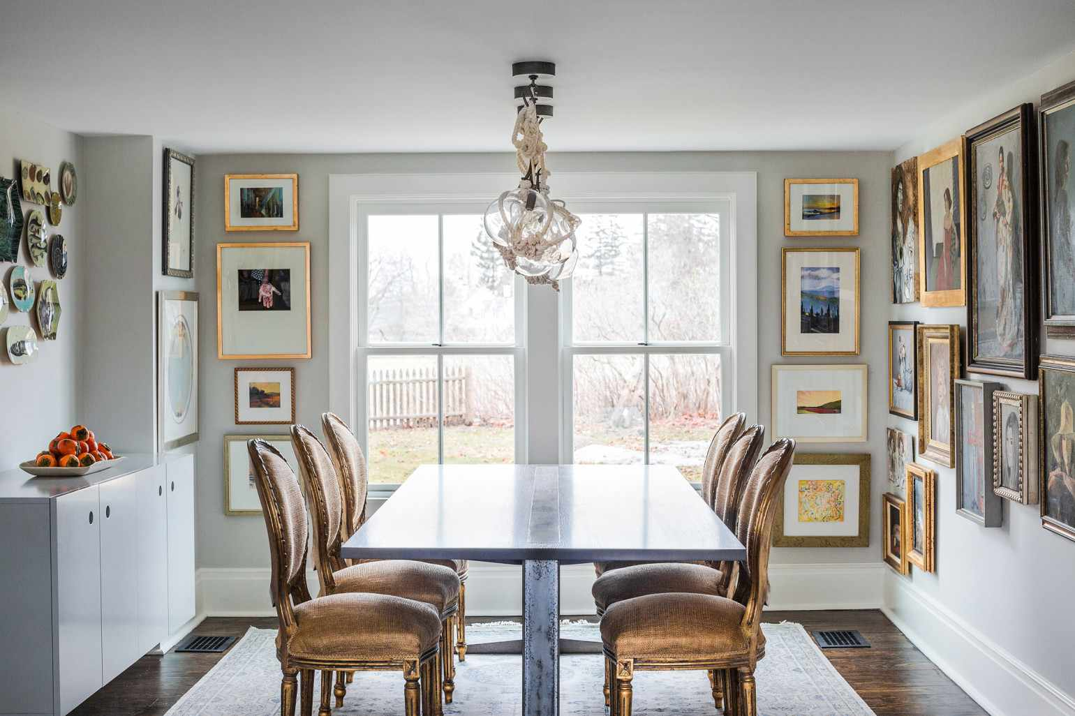 A dining room with a crafty centerpiece, made from globe lights, white rope, and several metal hooks