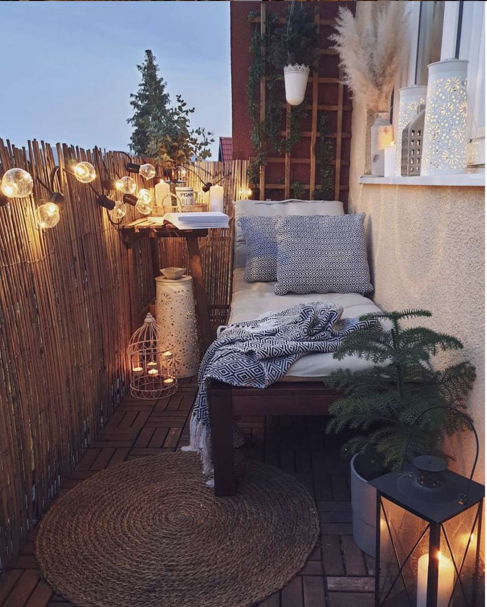 small balcony with privacy fence, elongated seating, small table, string lights hanging from privacy fence