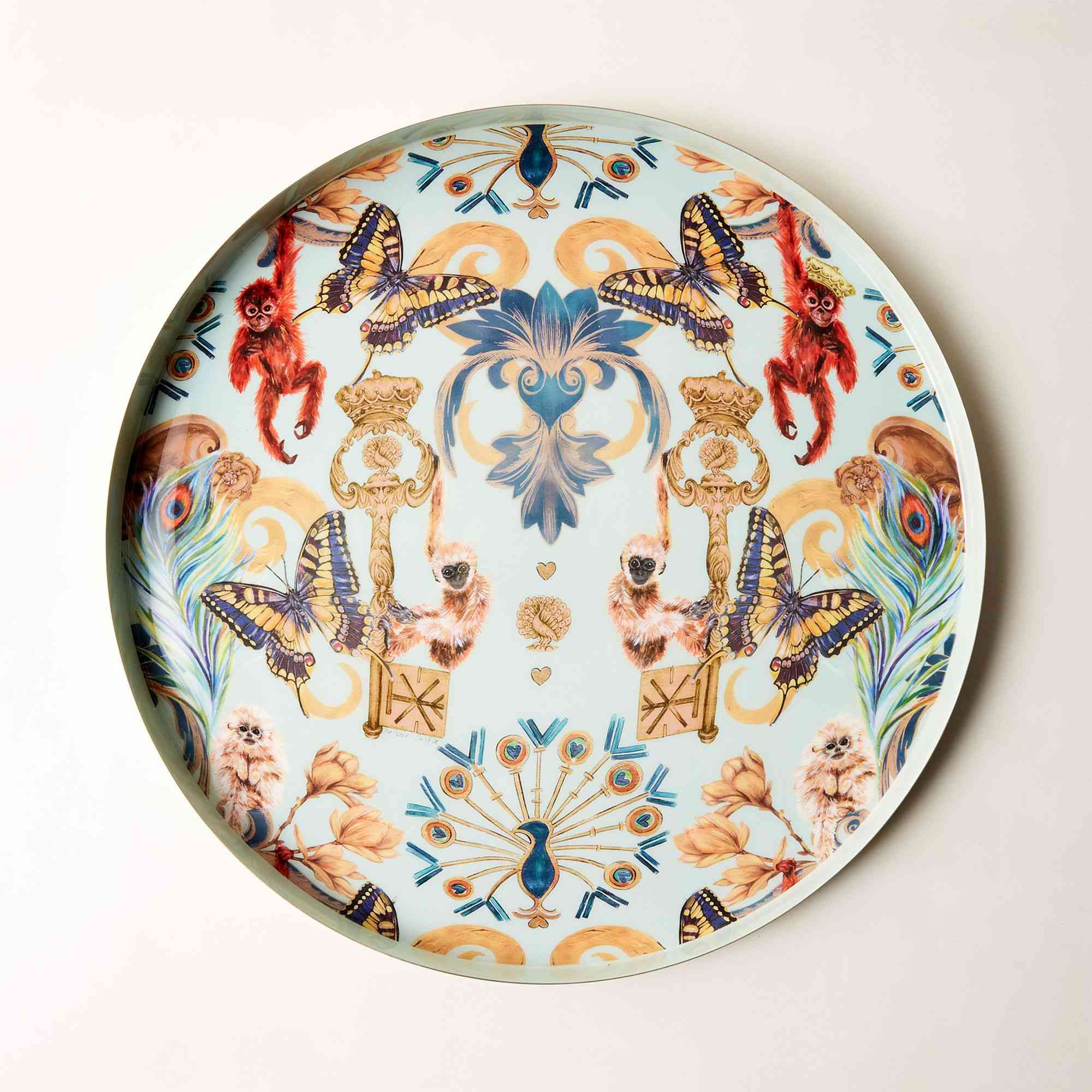 A round serving tray by CB2 featuring butterflies, monkeys, and peacocks on a light blue background.