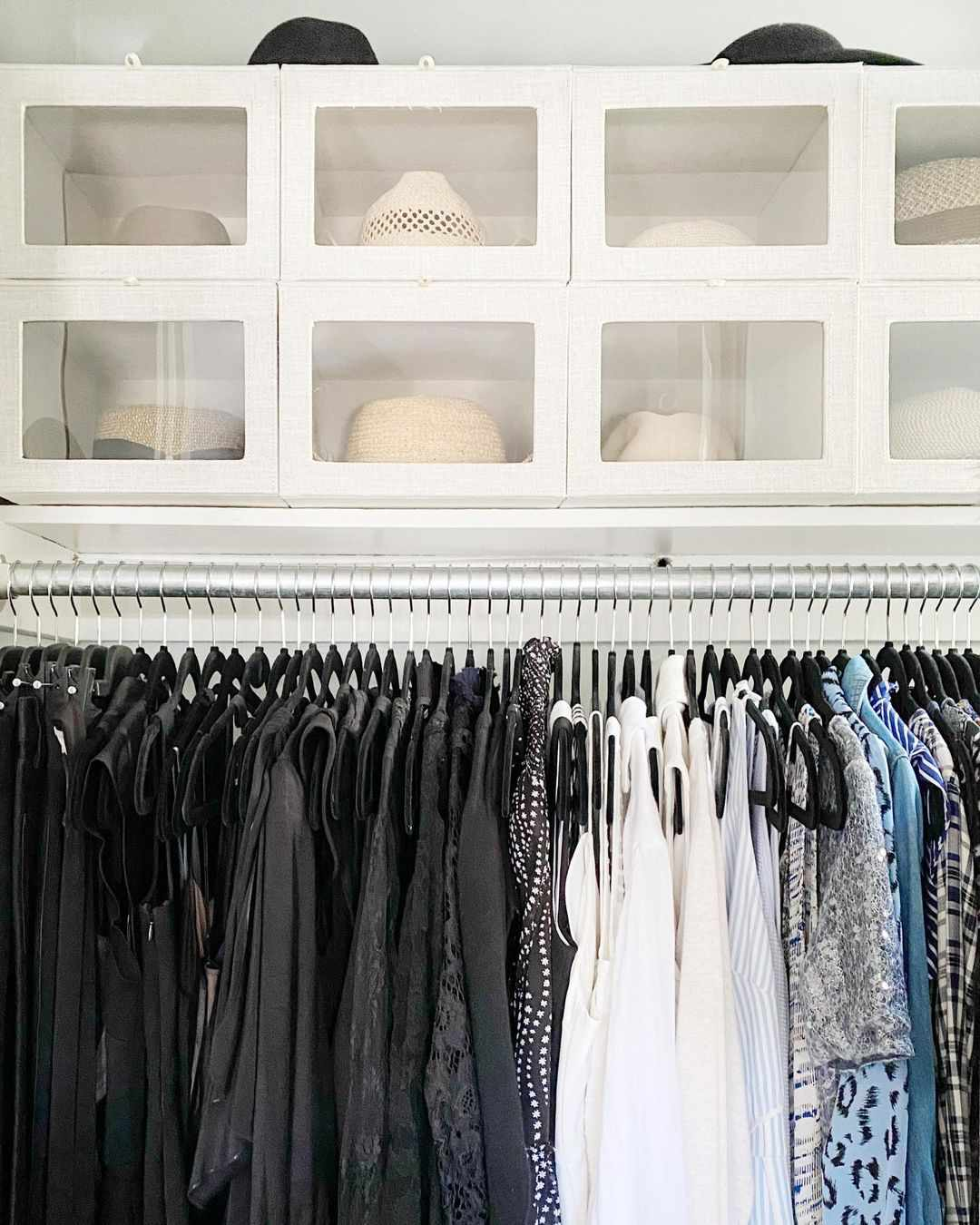 Closet with bins above the clothes