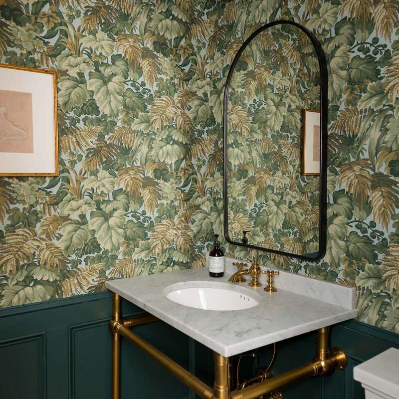 A powder room with intricate leafy wallpaper on the walls
