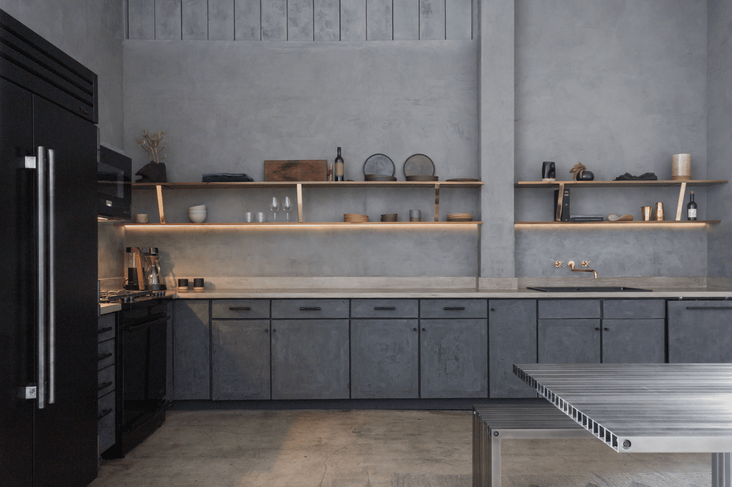 A kitchen with slate gray walls and cabinets
