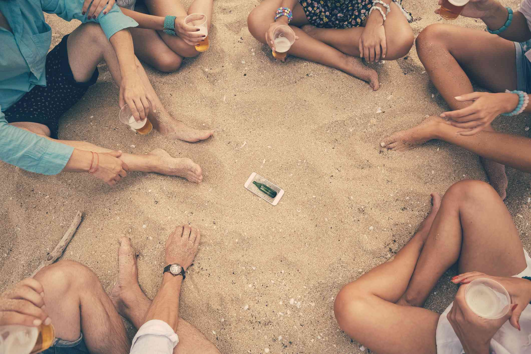 Young people play spin the bottle on the beach