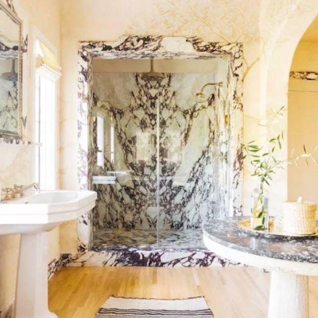 marble bathroom with light wood flooring, pedestal sink