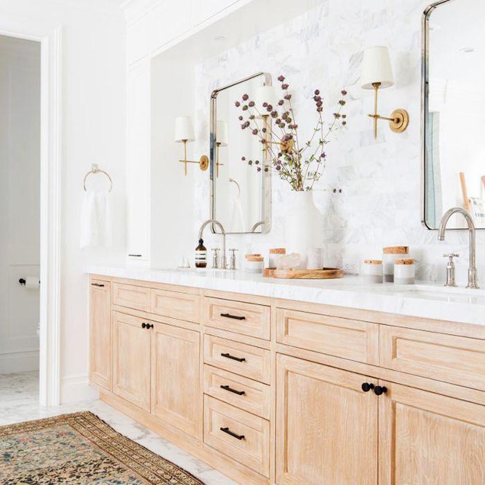 marble bathroom with recessed vanity, patterned area rug