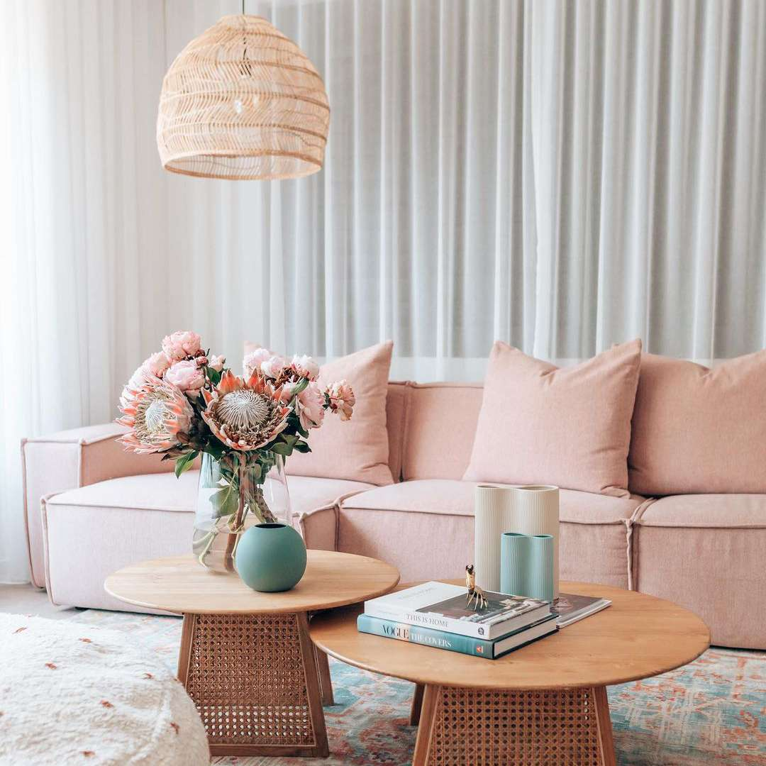 Pink sofa next to coffee table with faux floral bouquet.