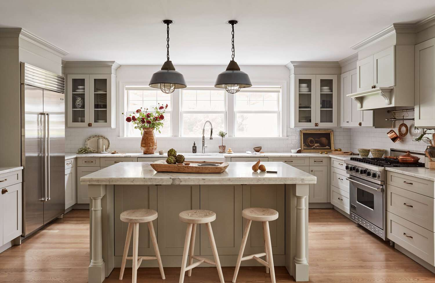 A rustic kitchen with mint green cabinets and farmhouse lighting fixtures